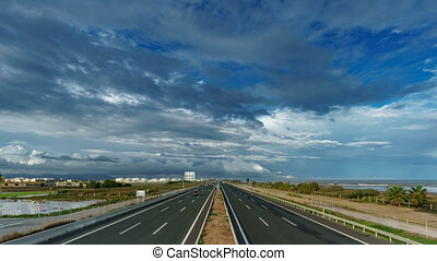 Top view time lapse of freeway near sea, cloudscape