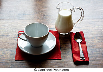 jug of milk with a empty cup on old wooden table