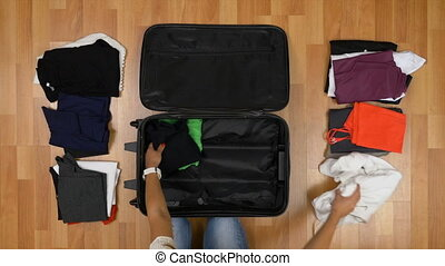 Top view travel concept of woman sorting and packing her clothes into suitcase