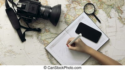 Top view traveler's hands picking a country for travelling at white wooden desk Travelling concept
