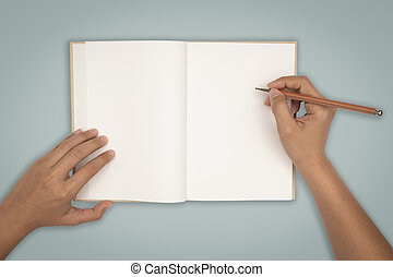 Top view- two hands hold a empty book spread