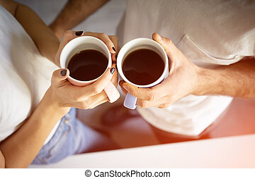 Top view. Two hands with cups coffee holding by young couple standing at the morning on the kitchen.