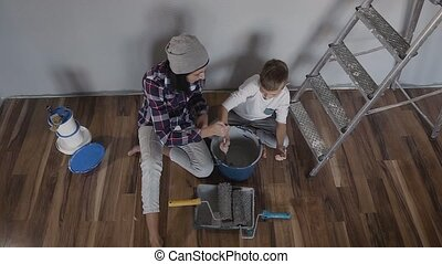 Top view. Two young people sit on the floor near the wall next to the ladder and mix the paint with mixer in the bucket. Repair in a new building. Whitewash in the flat