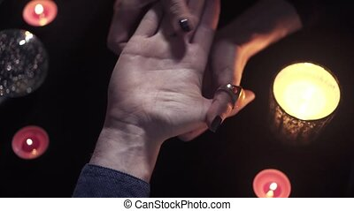 Top view unidentified woman fortune teller palmist with dark manicure divines on the hand of an unidentified young man. Concept of the desire to look into the future and find out your fate