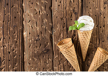 Top view white ice cream in waffle cone on brown rustic wooden background. photo of ice cream in a waffle cones over wooden background with copy space.