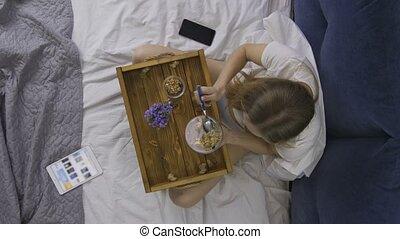 Top view woman eating healthy breakfast in bed