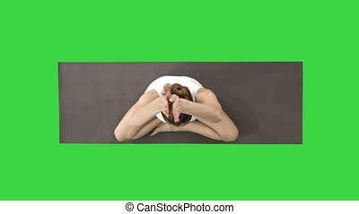 Woman folding legs in to lotus pose on a Green Screen,...