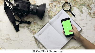 Top view woman traveler hands planning holiday using mobile...