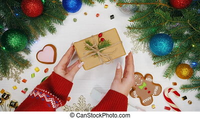 Top view. Woman's hands puts gift wrapped in craftool paper decorated with sprig of spruce and wild rose berries. Wooden white table decorated with Christmas stuff, garlands, gingerbread, lollipops