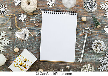 Top view wooden table with empty notepad mockup for Merry Christmas and Happy New Year 2020 text and twine, decorations and gifts. Xmas card concept with copy space