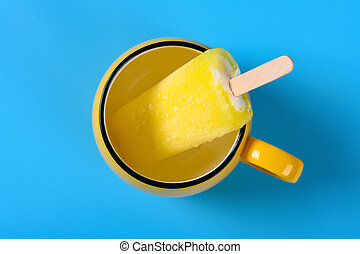 top view yellow popsicle in a cup on blue background