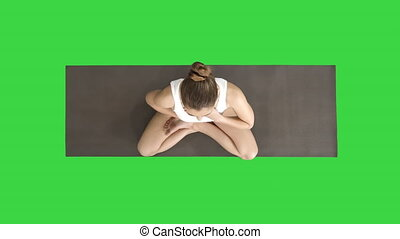 Yoga girl breathing in lotus pose with her hands on her...