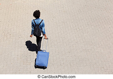 Top view young afro american woman walking on the street with luggage
