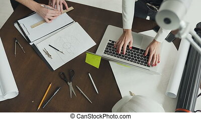 Top view. Young woman-architect and young designer, working on the project of new apartments. Engineer man and architect drawings blueprint at office. Female architect working on a laptop