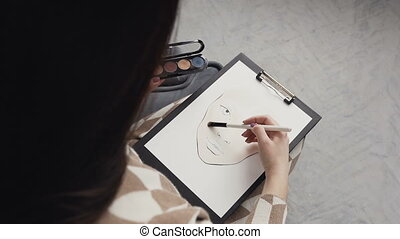Top view. Young woman makeup artist in a bright studio draws a face chart. The make-up artist draws a schematic image of a face on watercolor paper and using shadow palette and brush cosmeticks