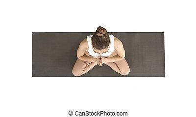 Young yogi woman practicing yoga, making namaste gesture in lotus pose, wearing white t-shirt on white background.