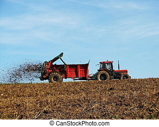 A farmer topdressing his field with dried manure