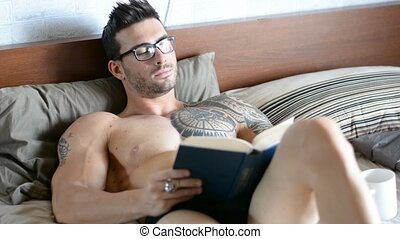 Topless man lying in bed and reading a book - Handsome...