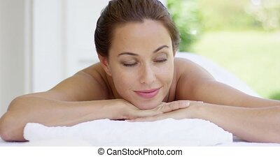 Topless woman looks to one side as she smiles while relaxing...