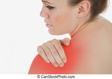 Closeup of topless woman massaging her shoulder against white background