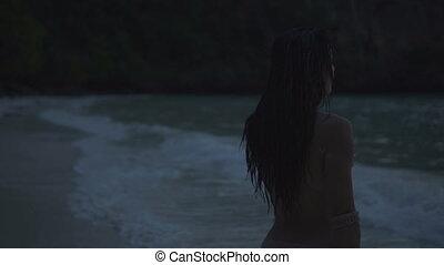 Topless woman walking on the beach