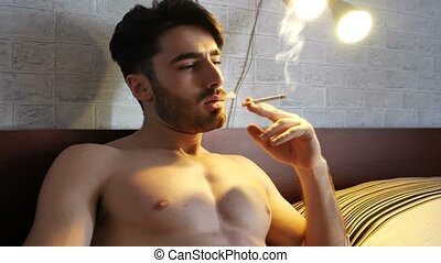 Topless young man smoking cigarette in bed - Topless...
