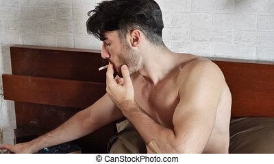 Topless young man smoking cigarette in bed