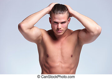 topless young man with hands in hair