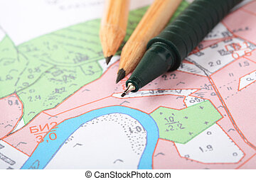 Topographic map with pencils and a RollerBall