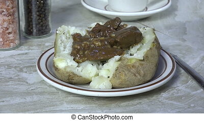 Topping a baked potato with beef tips and gravy - Spooning...