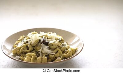 Topping cheese slices over tortellini al pesto on dotted ...