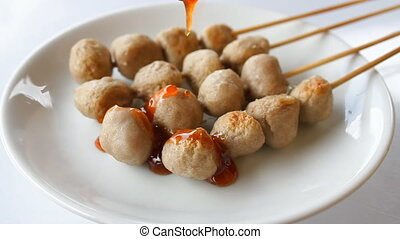 Topping traditional spicy sauce on pork ball