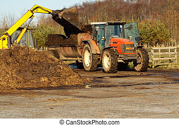 Topping up with manure - agricultural scene of farmer...