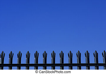 Tops of metal palisade fencing against a blue sky with space...