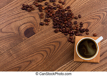 Topview cup of coffee and scattered coffee beans on wood. Flat lay spilled seeds on brown wooden surface.