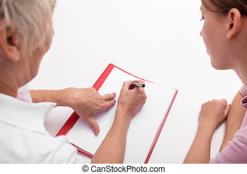topview of a doctor and patient, doing some paperworks