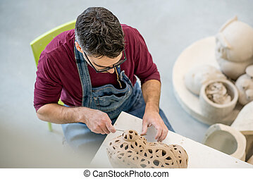 Topview of Ceramist Dressed in an Apron Sculpting Statue from Raw Clay in Bright Ceramic Workshop.