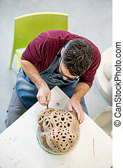 Topview of Ceramist Dressed in an Apron Sculpting Statue...