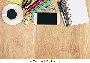 Top view of wooden desktop with coffee cup, blank smartphone, spiral notepad, colorful pencils and paper clips. Mock up