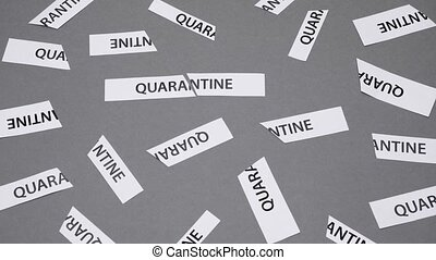 Pieces of torn paper with QUARANTINE word blown off the grey background. Word QUARANTINE printed on piece of papers tored apart as quarantine is over. Back to work. Quarantine is over
