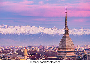 Torino (Turin, Italy): cityscape at sunrise with details of the Mole Antonelliana towering over the city. Scenic colorful light on the snowcapped Alps in the background.