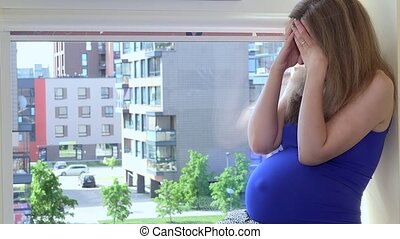 Tormented sad pregnant woman sitting on window sill at home