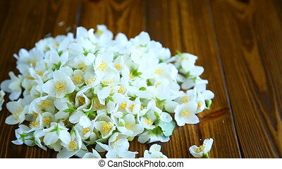 torn blossoming jasmine flowers on a wooden table