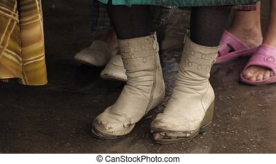Torn boots on a homeless woman - Homeless woman in old shoes...