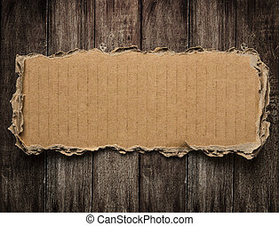 Torn cardboard on wood background