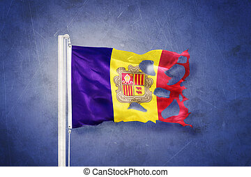 Torn flag of Andorra flying against grunge background