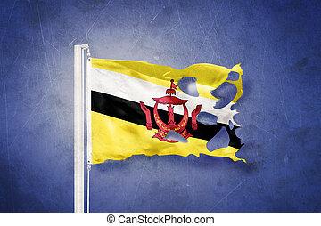 Torn flag of Brunei flying against grunge background