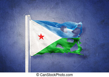 Torn flag of Djibouti flying against grunge background