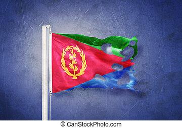Torn flag of Eritrea flying against grunge background