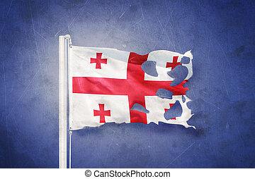 Torn flag of Georgia flying against grunge background